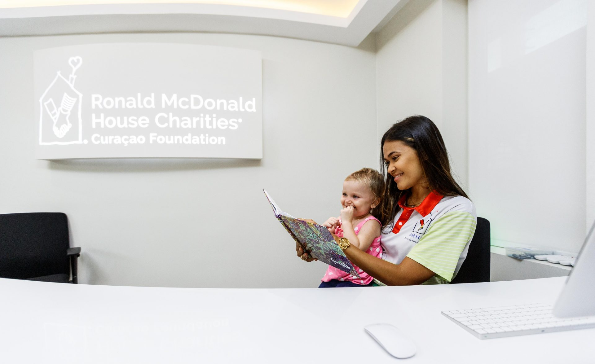 Female volunteer reading a book with a child patient